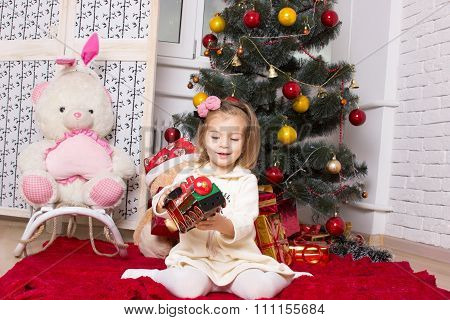 The Girl With A Toy Engine And Gifts Under A Christmas Fir-tree