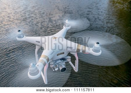 FORT COLLINS, CO, USA, October 18, 2015:  Radio controlled Phantom 3 quadcopter drone flying with a camera over a lake.