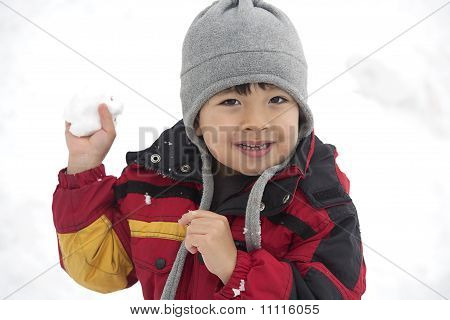 Young boy with snowball in hand.