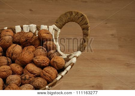 Basket full of walnuts on the wooden floor