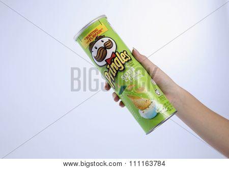 kuala lumpur-malaysia, 16th november 2015, female's hand holding a tube of the sour cream pringles potato chips