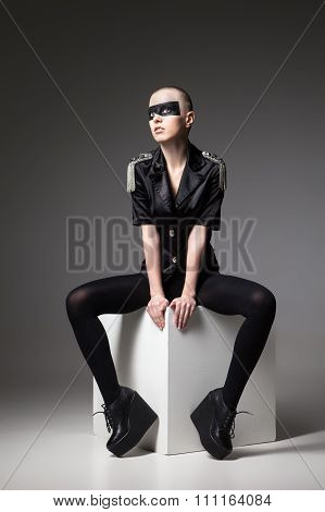agressive bald sitting woman with mask makeup