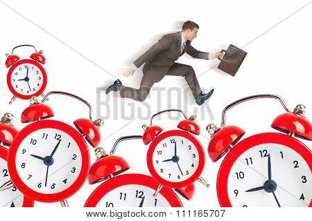Businessman running on alarm clocks