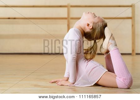 Little girl is busy exercising on the floor