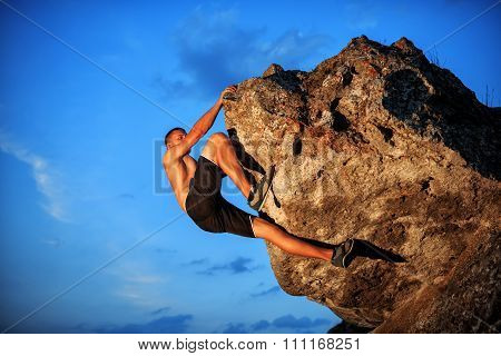 Free climber holding on the cliff