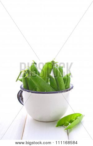 Young Green Peas In A Metal Colander On A White Background