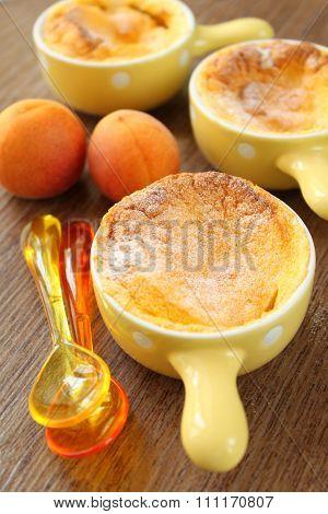 baked peach dessert souffles on a dark wooden background