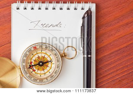 Notepad with handwritten word Trends, compass and pen on wooden board top view have place for text