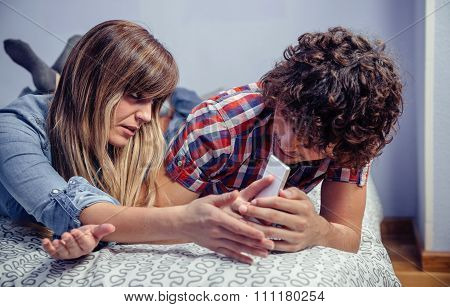 Man looking messages in smartphone of angry woman