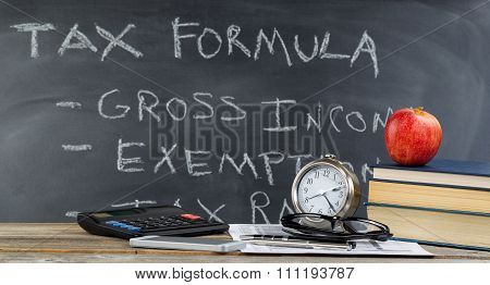 Desktop And Chalkboard For Learning How To Do Income Taxes In Classroom