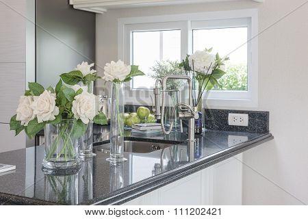 Glass Vase Of Flower On Black Granite Counter