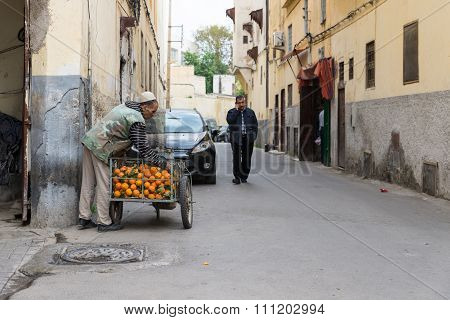 One Man Sells Orange While Another Man Talks To The Mobile Phone