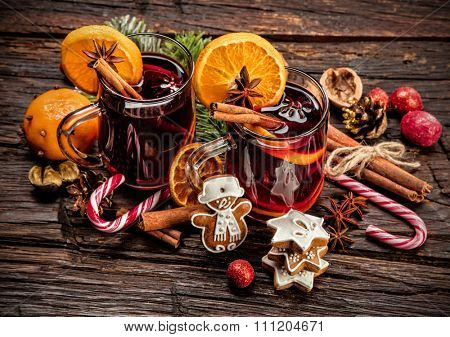 Hot wine drinks with spicy and sweet arrangement, Shot on old wooden table