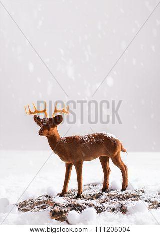 Reindeer animal figure on snowy wooden log
