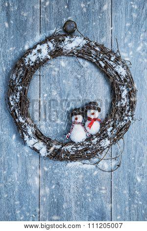 Winter garland hanging on rustic wooden door with snowmen decoration
