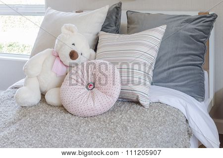 Kid's Bedroom With Pillows And Dolls On Bed