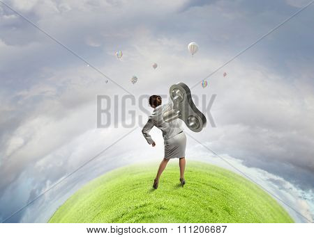 Young businesswoman walking with wind up key in his back