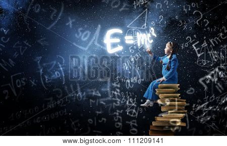 Little cute girl sitting on pile of books and pointing with finger