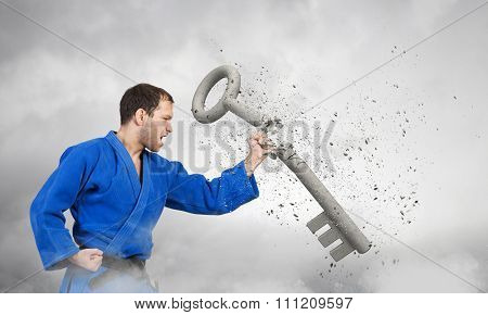 Young determined karate man breaking with anger concrete key