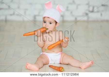 Portrait of a cute baby dressed in bunny ears sitting and eating  carrot.