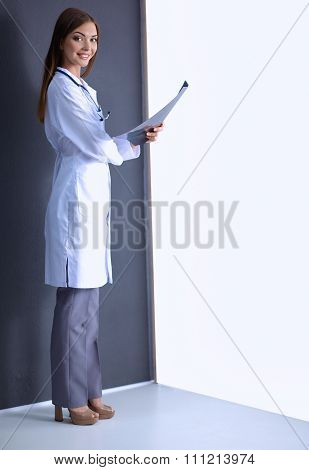 Female doctor with X-ray picture standing near grey wall