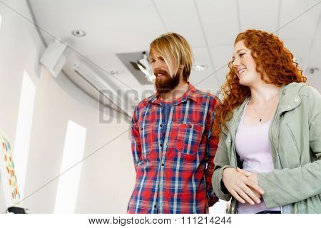 Young caucasian couple standing in a gallery and contemplating abstract artwork