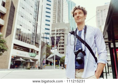 Happy male tourist in city walking with camera