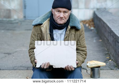 Homeless man holding a cardboard sign.