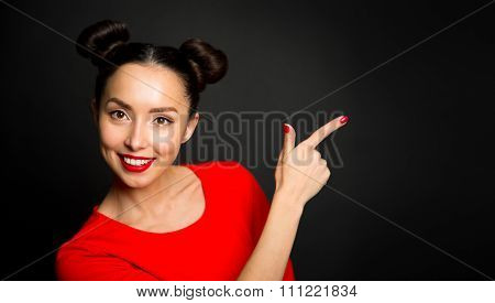 Portrait Of Young Excited Woman Pointing Forefingers Over Black Background