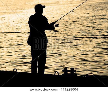 Fisherman Standing On Edge Of Dock With Fishing Rod Near River In City Warm Filtered