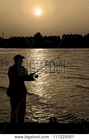 Fisherman Standing On Edge Of Dock With Fishing Rod Near River And Beach Town In Rays Of Yellow Suns