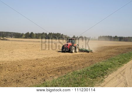 Modern tractor plowing the field in spring