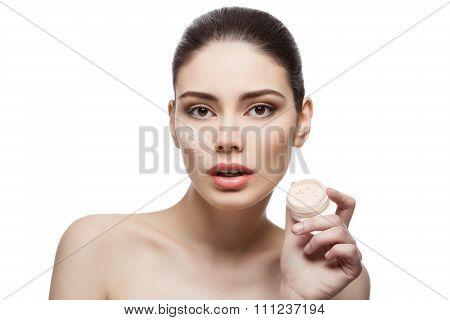 Beautiful girl holding jar with loose powder