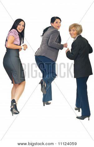 Vista posterior de mujeres corriendo y mirando hacia atrás