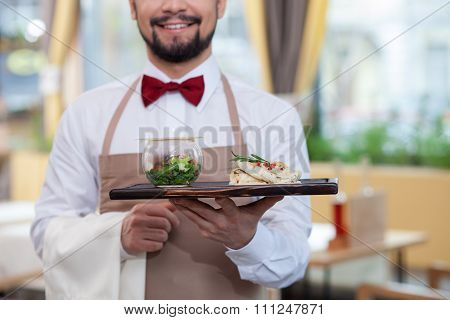 Cheerful male cafe worker is serving supper