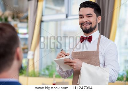 Handsome male cafe worker is waiting a client