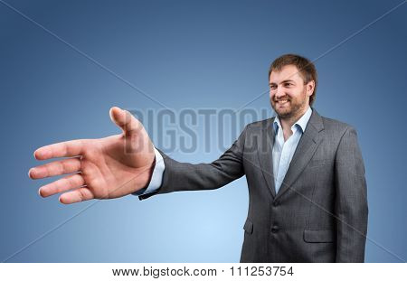 Businessman offers his big hand for handshake over blue