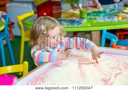 Cute Child Girl Drawing Draws Developing Sand In Preschool At Table In Kindergarten By Method Of Mon
