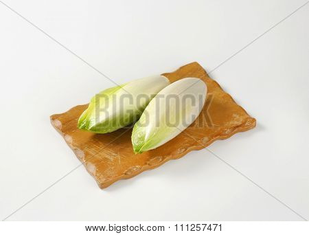 heads of fresh belgian endive on wooden cutting board
