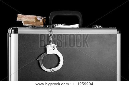 Handcuffs chained to silver case with money
