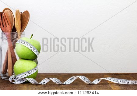 Green Apple With Measuring Tape On Wooden Background In Concept Of Healthy And Diet