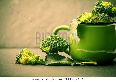 Still Life With Fresh Green Broccoli In Ceramic Cup On Black Stone Plate