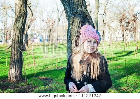 Little Girl In Pink Hat And Jacket Standing Near Tree, Park