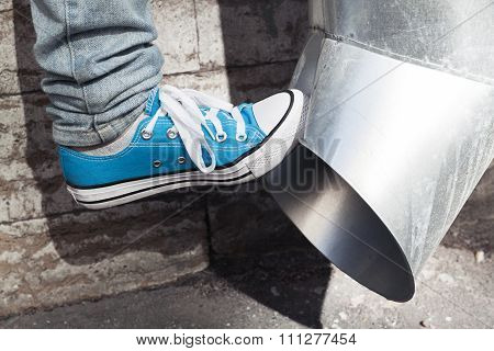 Teenager In Blue Sneakers Kicks Drainpipe