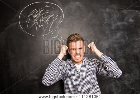 Angry Young Man In Rage Standing Against The Background Of Chalkboard