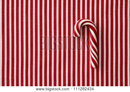 Peppermint candy cane on striped background