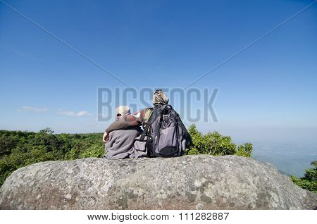 Two Brothers Are Sitting On A Big Rock In The Mountains