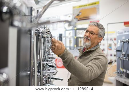 Senior man choosing a bathroom/kitchen tap in a home furnishings retail store