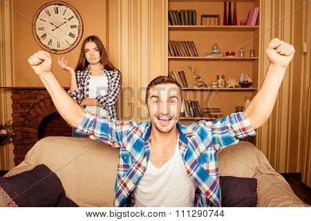 Joyful Man Rooting For His Favorite Team, While His Wife Is Dissatisfied