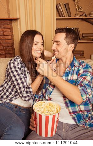 At Home Girl And Guy Feeding Each Other Popcorn And Watching A Movie At Home